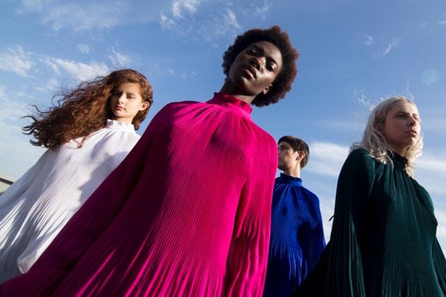 Skupina žien v bielych, modrých, zelených a ružových šatách