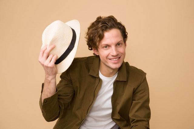 Muž v kaki bunde, bielom tričku a bielym klobúkom v ruke.jpg