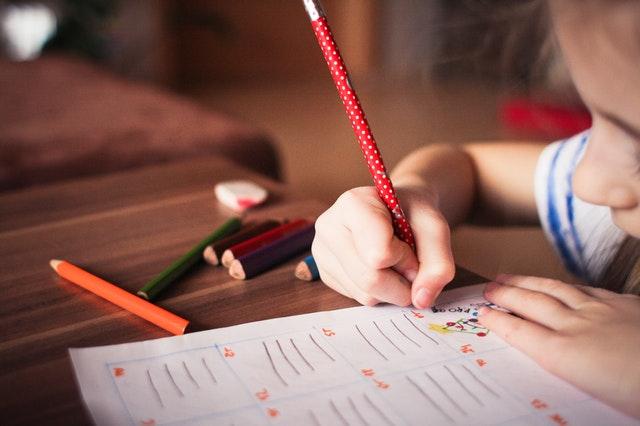 Dieťa píše na papier pri drevenom stole.jpg