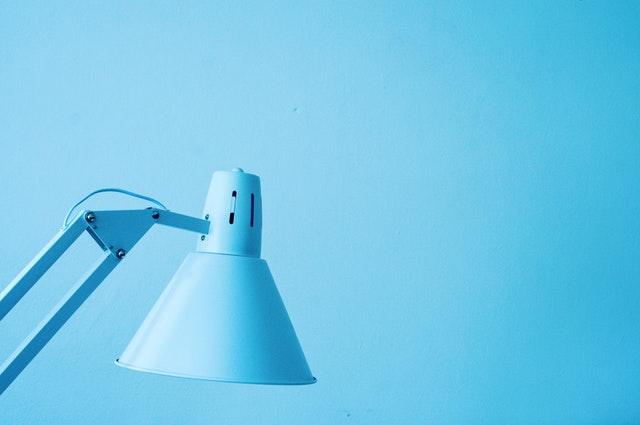 Modrá stolová lampa pred modrou stenou.jpg