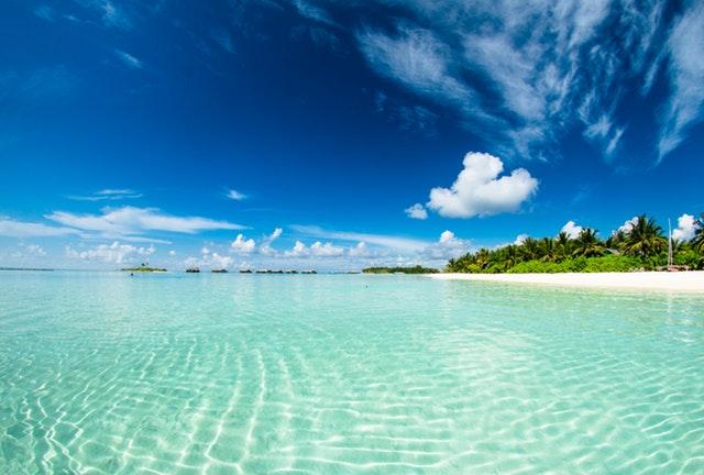 Priezračné more, pláž s bielym pieskom a zeleňou a modré nebo s bielymi oblakmi