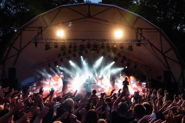 Na pódiu hrá kapela, dav fanúšikov