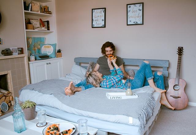 Muž a žena raňajkujú na manželskej posteli v spálni