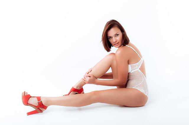 Žena v bielom erotickom body. V červených topánkach na podpätku sedí na zemi.jpg