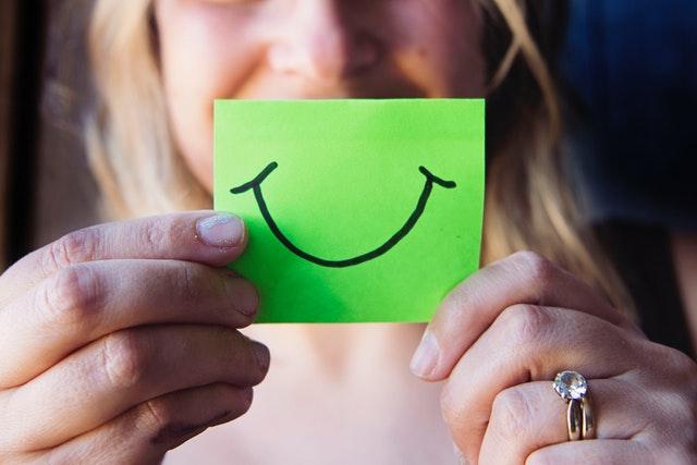 Žena si drží pred tvárou papierik s úsmevom.jpg