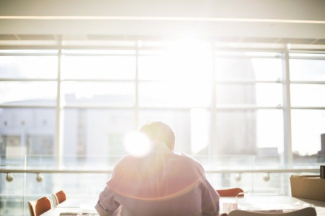 Muž sedí pred obrovským oknom, cez ktoré svieti slnko.jpg