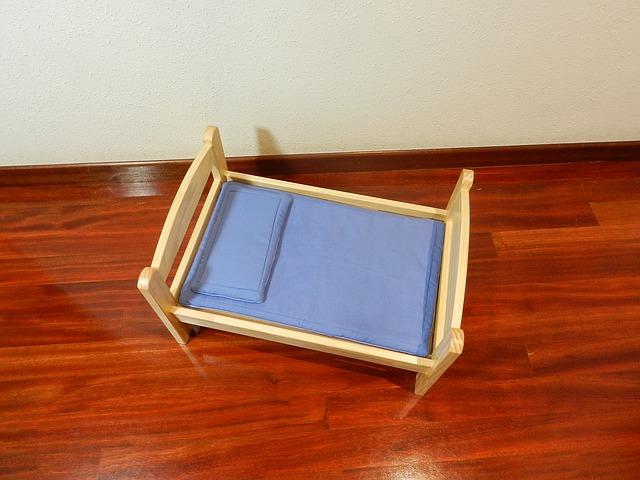 Zdrobnenina drevenej postele s modrým matracom a vankúšom