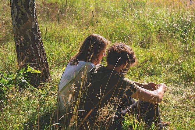 Muž a žena spolu sedia v tráve